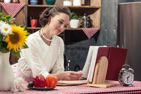 smiling attractive housewife in vintage clothes reading recipe book at kitchen