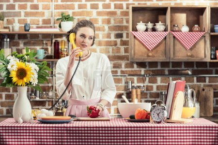 beautiful adult housewife talking by phone during meal preparation at kitchen