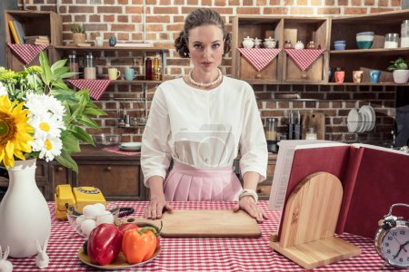 serious adult housewife in vintage clothes looking at camera at kitchen