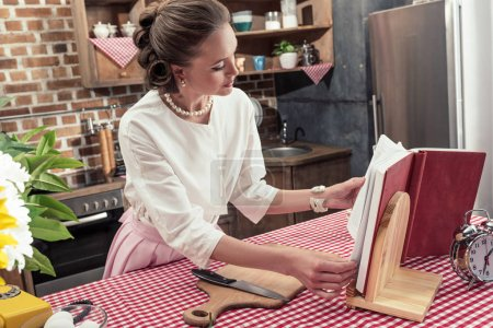 attractive adult housewife in vintage clothes reading recipe book at kitchen