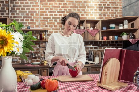 concentrated adult housewife cutting red bell pepper at kitchen