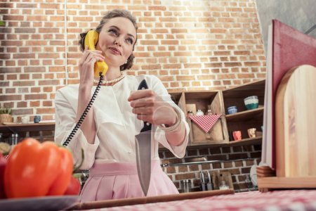 bottom view of smiling adult housewife with knife talking by yellow wired phone at kitchen