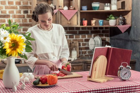 smiling adult housewife cutting bell pepper at kitchen