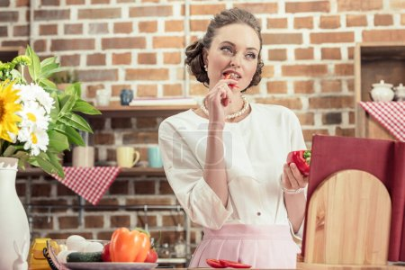 attractive adult housewife eating raw bell pepper an looking away at kitchen
