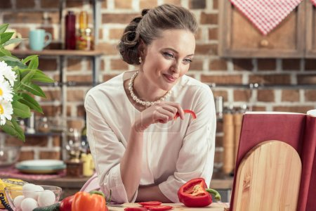 smiling adult housewife reading recipe book and tasting fresh vegetables at kitchen