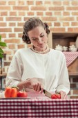attractive adult housewife in vintage clothes cutting tomato at kitchen