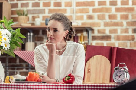 thoughtful adult housewife leaning on table and looking away at kitchen