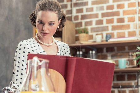focused adult housewife in vintage clothes reading recipe book at kitchen