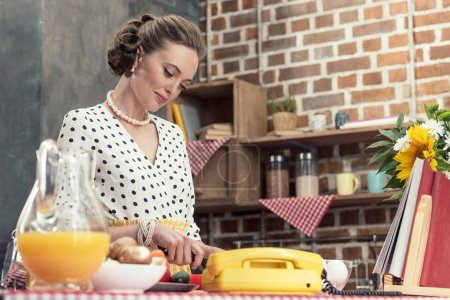 beautiful adult housewife in vintage clothes cooking at kitchen