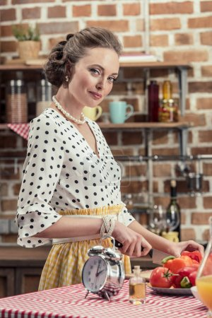 smiling adult housewife cutting bell pepper and looking at camera at kitchen