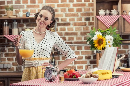 happy adult housewife holding jug of orange juice and looking at camera at kitchen
