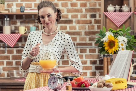 smiling adult housewife holding jug of orange juice and looking at camera at kitchen