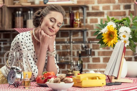 happy adult housewife with closed eyes leaning on table at kitchen