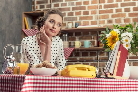 thoughtful adult housewife leaning on table at kitchen