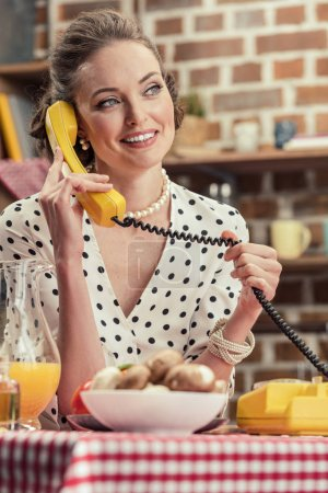 happy adult housewife talking by vintage wired phone at kitchen