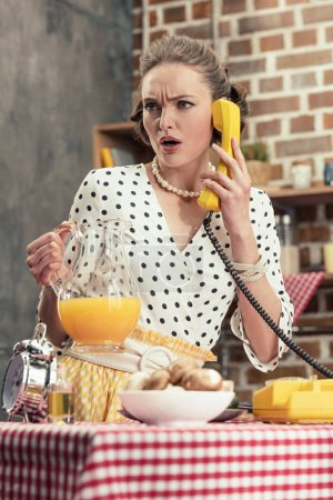 confused adult housewife talking by vintage wired phone at kitchen