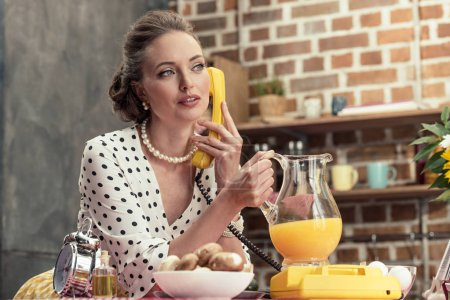 attractive adult housewife holding jug of orange juice talking by vintage wired phone at kitchen