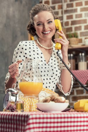 smiling adult housewife holding jug of orange juice talking by vintage wired phone at kitchen