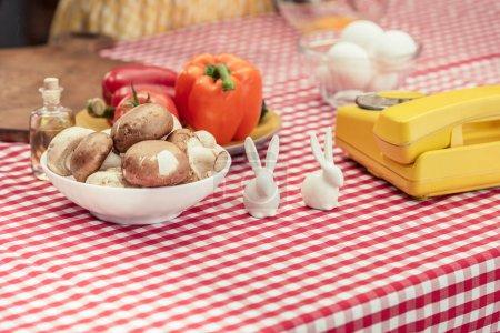 Foto de Close-up foto de teléfono vintage con varias verduras y conejitos de porcelana de mesa - Imagen libre de derechos