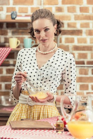 attractive adult housewife whisking eggs for omelette and looking at camera at kitchen
