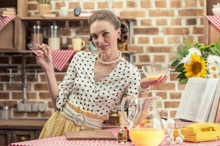 happy adult housewife with glass bowl and whisk looking at camera at kitchen
