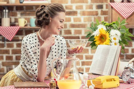 smiling adult housewife with bowl reading recipe book at kitchen