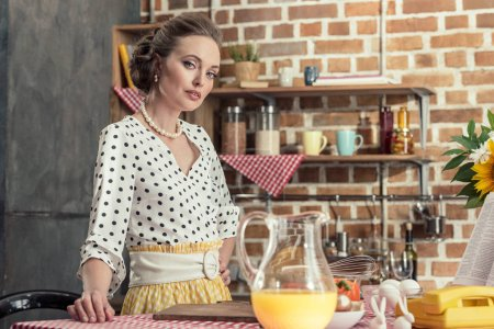 beautiful adult housewife standing at kitchen and looking at camera