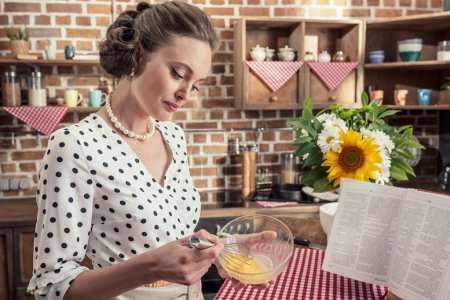 confident adult housewife whisking eggs for omelette at kitchen