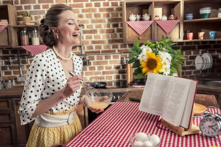side view of laughing adult housewife whisking eggs for omelette at kitchen