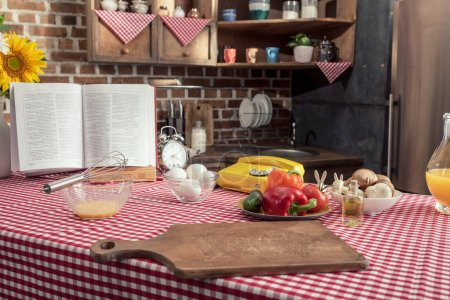 various uncooked products and recipe book on cooking table at kitchen
