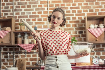 Photo for Beautiful adult housewife with bowl of dough and rolling pin looking at camera at kitchen - Royalty Free Image