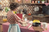 attractive adult housewife preparing dough in glass bowl at kitchen