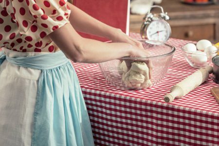 cropped shot of housewife preparing dough in glass bowl at kitchen