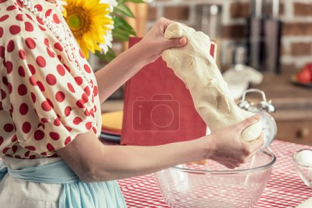 cropped shot of housewife kneading dough with hands at kitchen