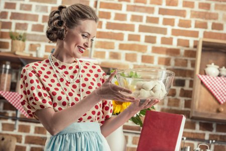 Photo for Happy adult housewife looking at dough in glass bowl at kitchen - Royalty Free Image