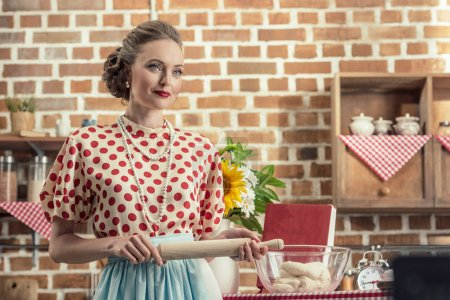 smiling adult housewife with rolling pin looking away at kitchen