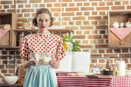 beautiful adult housewife holding bowl of dough and looking at camera at kitchen