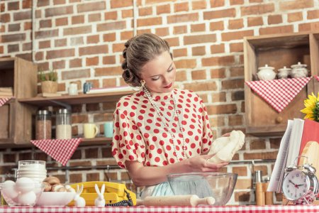 beautiful adult housewife with dough for baking at kitchen