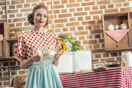 beautiful adult housewife holding bowl of dough and looking away at kitchen