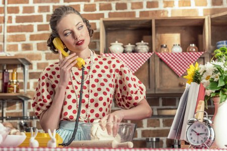 attractive adult housewife talking by phone and kneading dough at kitchen