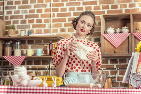 attractive adult housewife kneading dough and looking at camera at kitchen