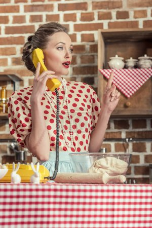 surprised adult housewife with creative idea talking by phone and pointing up at kitchen