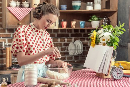 beautiful adult housewife spilling flour onto dough in bowl at kitchen