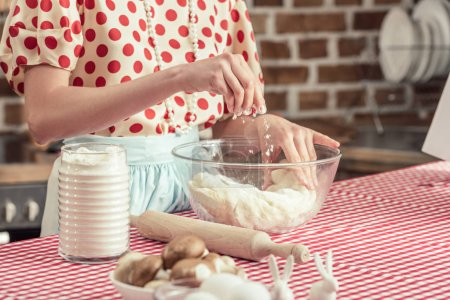 cropped shot of housewife spilling flour onto dough in bowl at kitchen