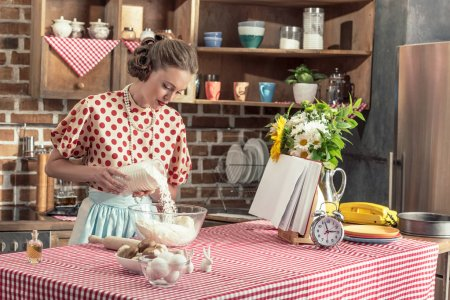 attractive adult housewife pouring flour into bowl for dough at kitchen
