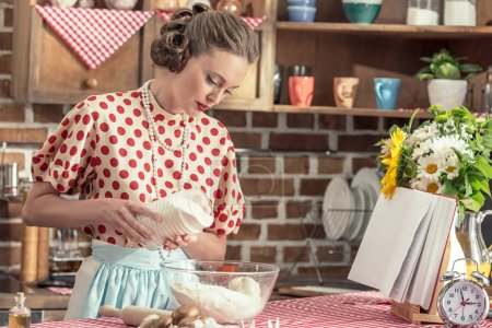 beautiful adult housewife pouring flour into bowl for dough at kitchen