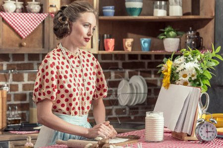 beautiful adult housewife kneading dough with hands at kitchen