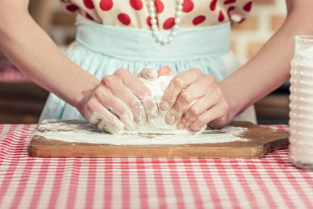 cropped shot of woman kneading dough with hands on wooden cuting board