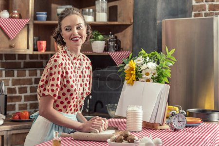 smiling adult housewife kneading dough with hands and looking away at kitchen