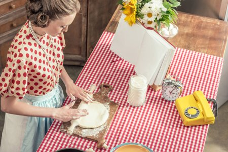high angle view of beautiful adult housewife kneading dough with rolling pin at kitchen